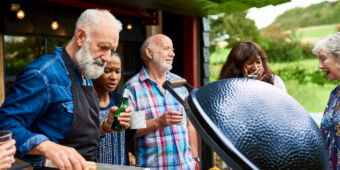 An older man is grilling vegetables at garden party with his family