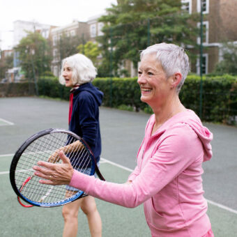 Two women playing tennis together