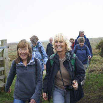 A group of smiling, middle-aged women and men hiking through farmland