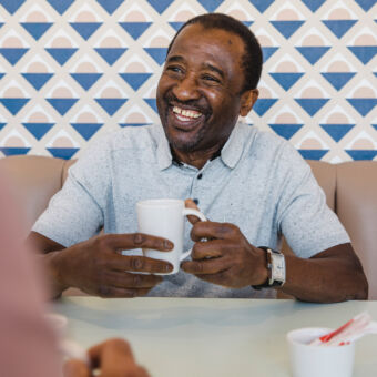 A happy middle-aged man holding a cup of tea in a cafe